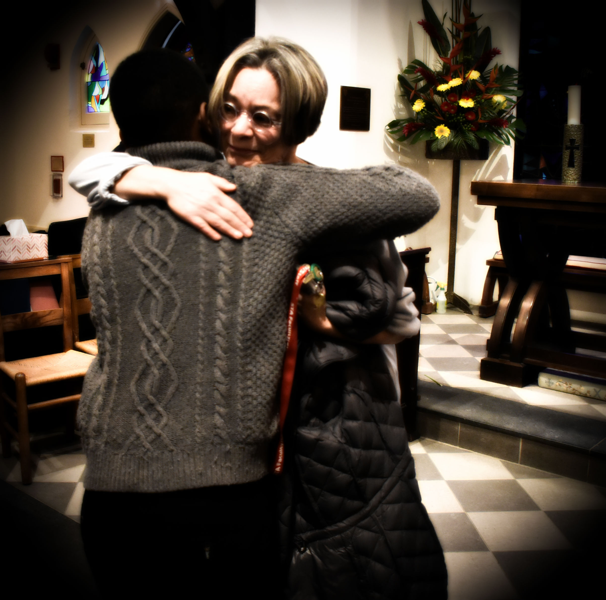 A goodbye hug by a teacher and her student inside a chapel after a service.